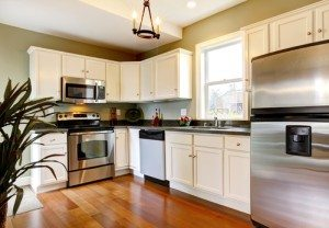 Classic white and green new kitchen with cherry floor.